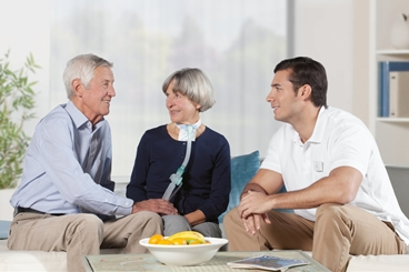 Homecare, Ventilation patient sitting on a couch in her living room with ventilation device, smiling, together with her husband and a male nurse, information