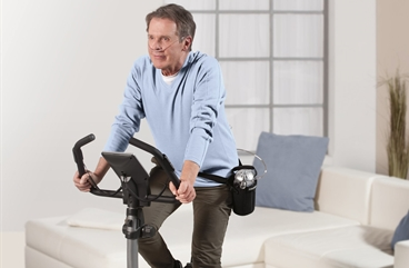 Homecare, Oxygen patient training on a exercise bike in his living room with nasal cannula, wearing his device in a bag