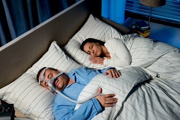 Patient with CPAP mask is sleeping soundly next to his wife in the bedroom.