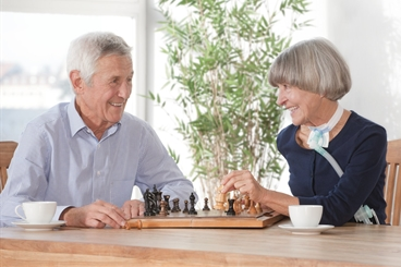 Homecare, Ventilation patient sitting on a table in her living room with ventilation device,  together with her husband playing chess